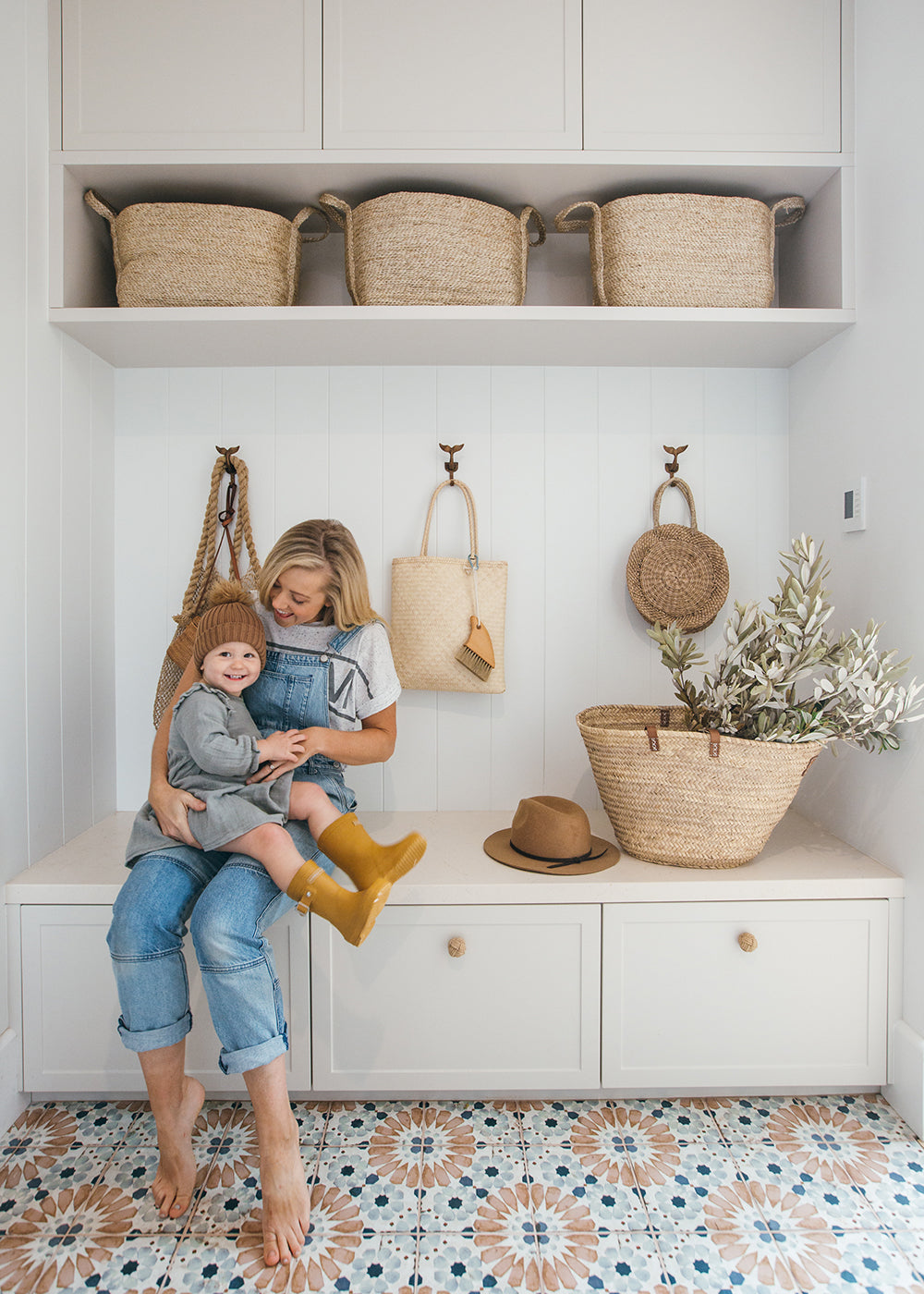 Woven baskets in Kara Demmrich's mudroom. Kara & her son playing in the foreground.