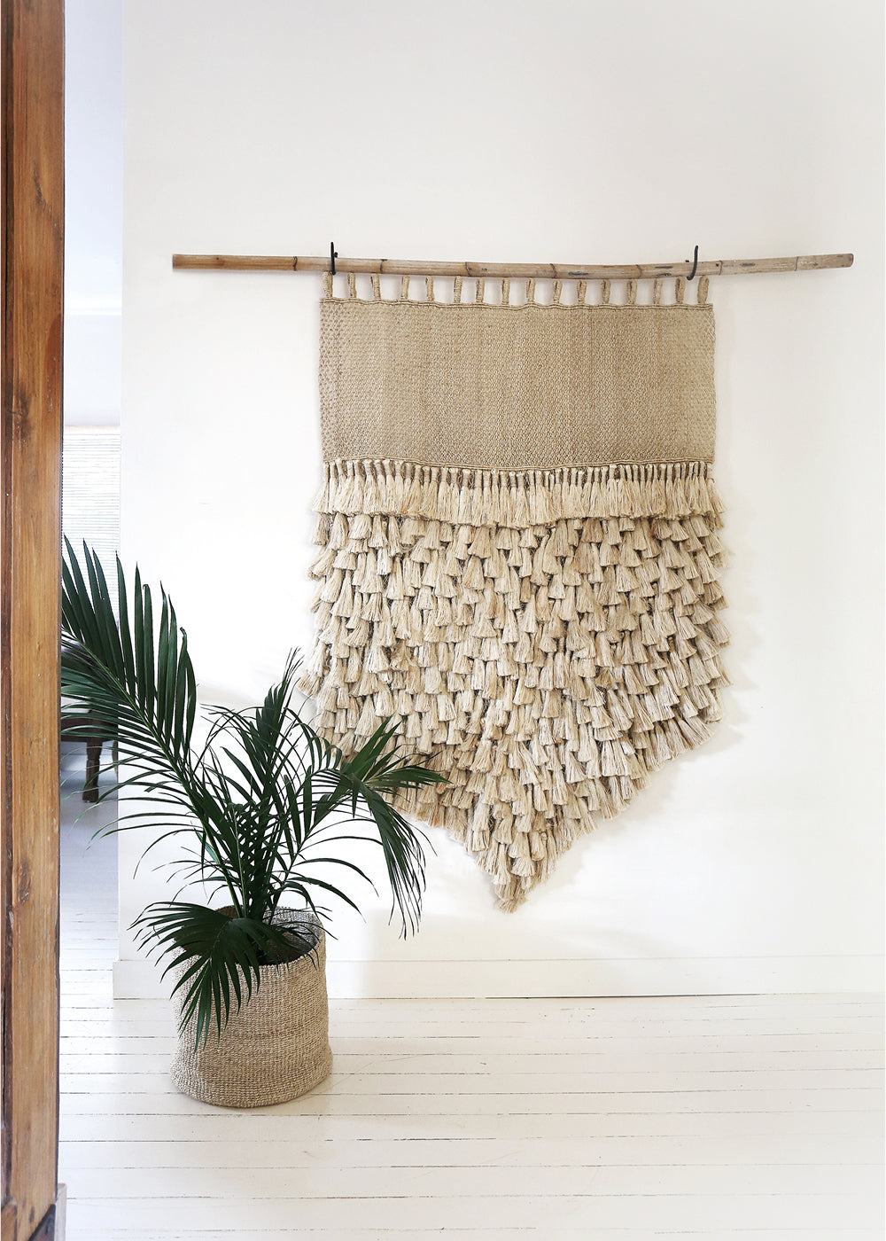 woven wall hangings - how they enhance any space. Natural jute tassel jumbo wall hanging on white wall.