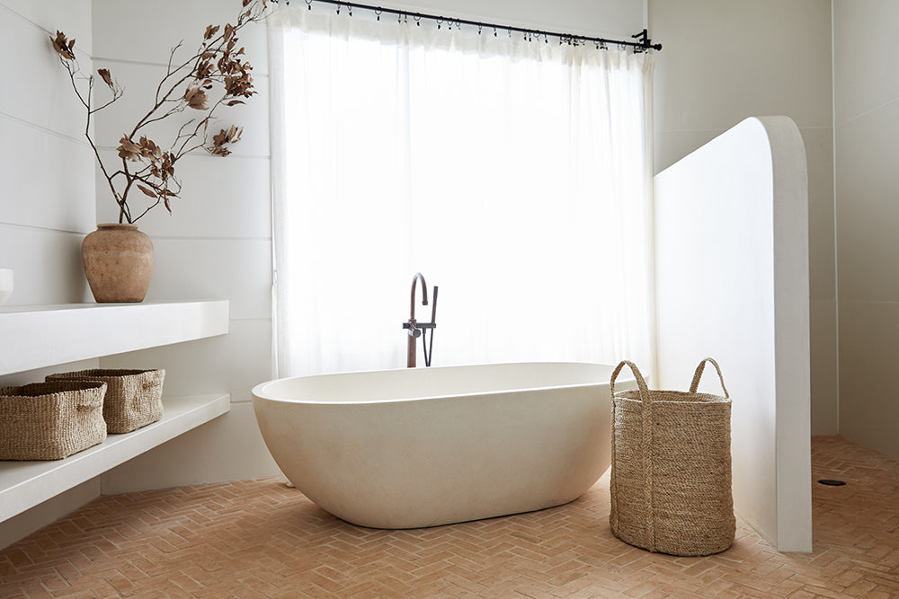 Medium jute storage basket used in a bathroom for storing towels, cosmetics and cleaning products.