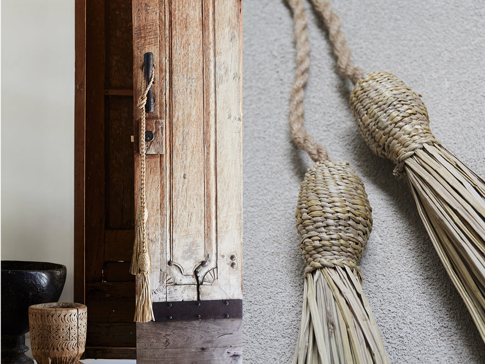 Natural home decor featuring handmade tassels and a heavy wooden door.