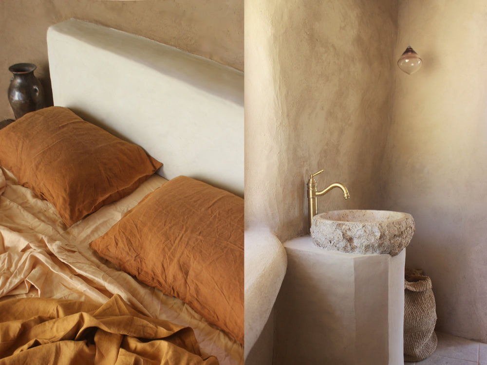 Maison de Base - Natural ochre coloured bed sheets. Hand moulded clay basin.