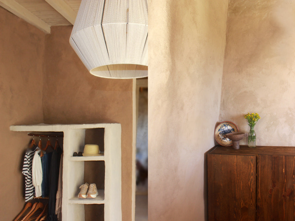 Maison de Base - Natural light shade hanging above a clay dresser with clothes and shoes.