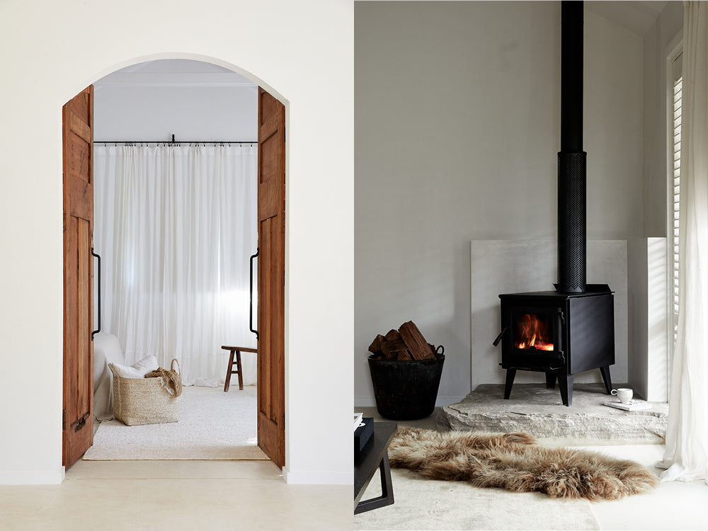 Looking into a living area with a handwoven jute basket on the ground. Black wood burning fireplace.