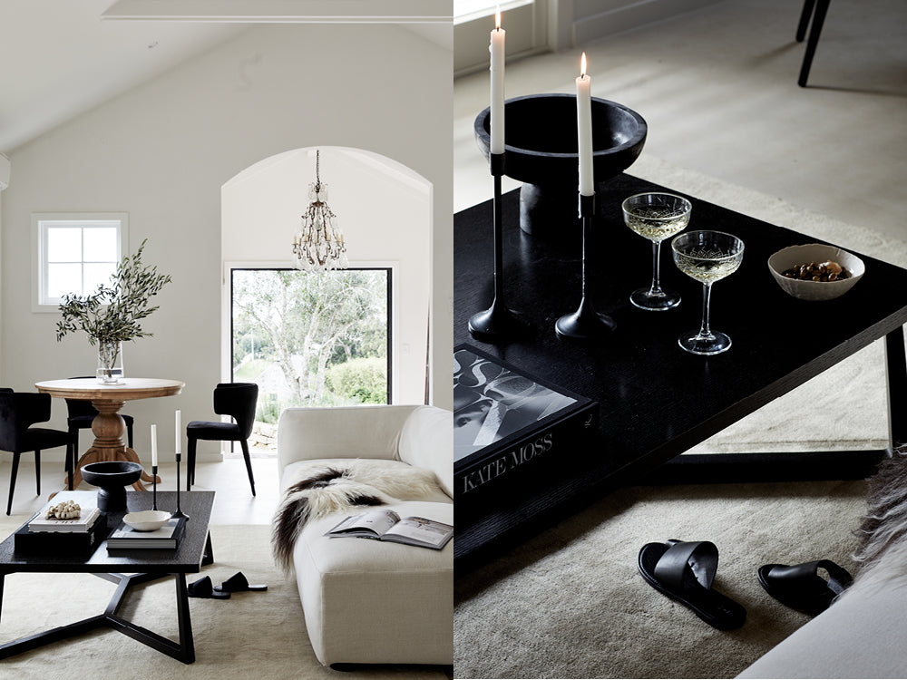 A living area at Le Viti in neutral tones. Close up of black coffee table with candles and glasses of sparkling wine.