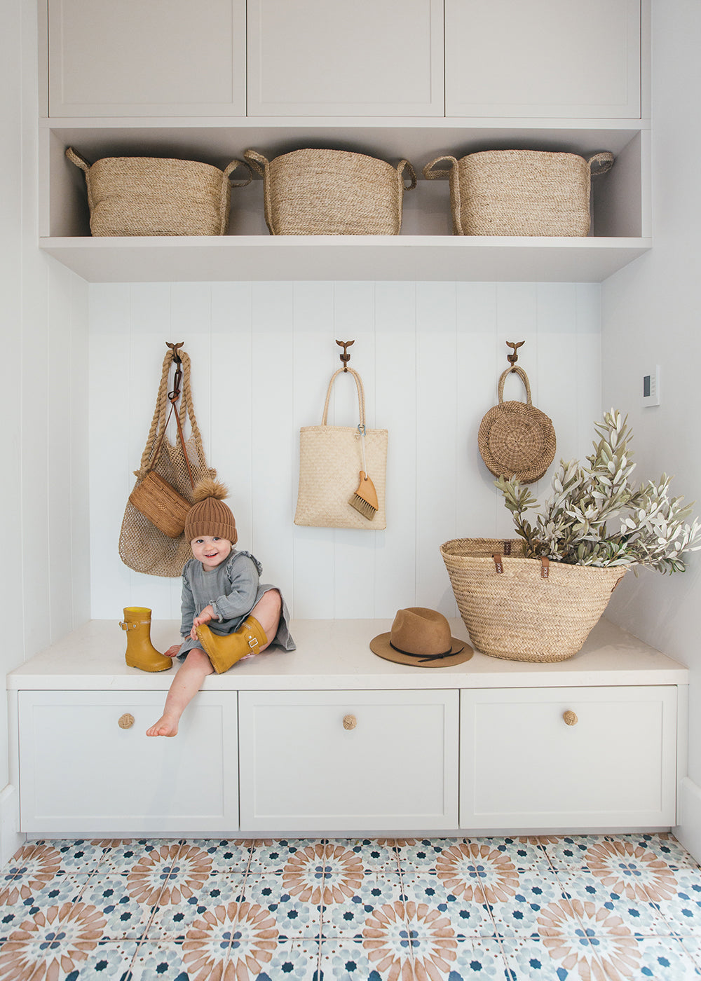 Woven baskets in Kara Demmrich's mudroom. Kara's son taking off his boots in the foreground.