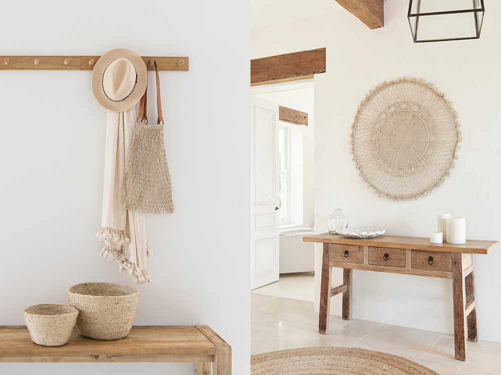 Hooks in an entry way with handwoven jute baskets for organisation and string hemp bag hanging on hook. Entryway console table with round jute rug, woven mandala wall hanging.