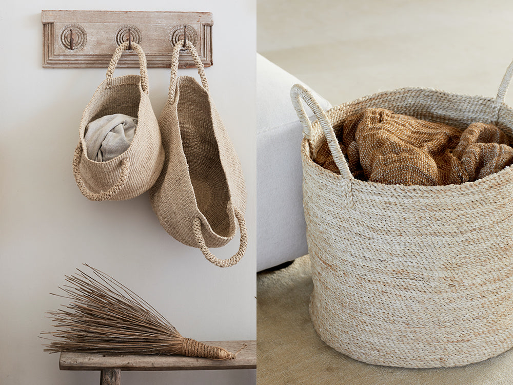Hooks on wall with hanging jute baskets, Decorative broom on entryway bench. Woven jute storage basket with fabric inside.