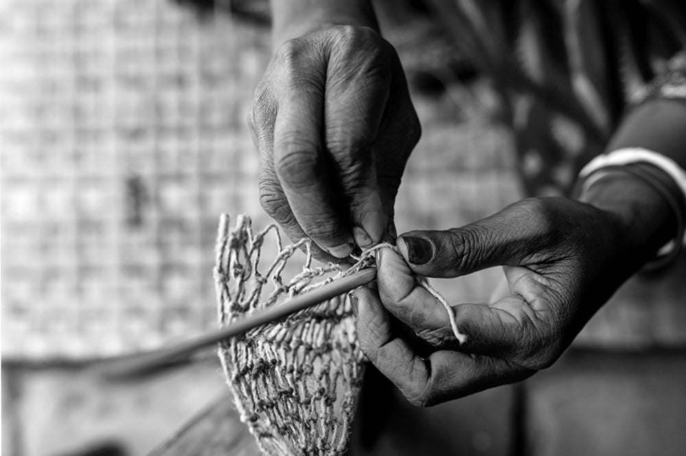 Fair trade artisans -  Bangladeshi woman weaves natural jute, close up on her hands as she weaves.