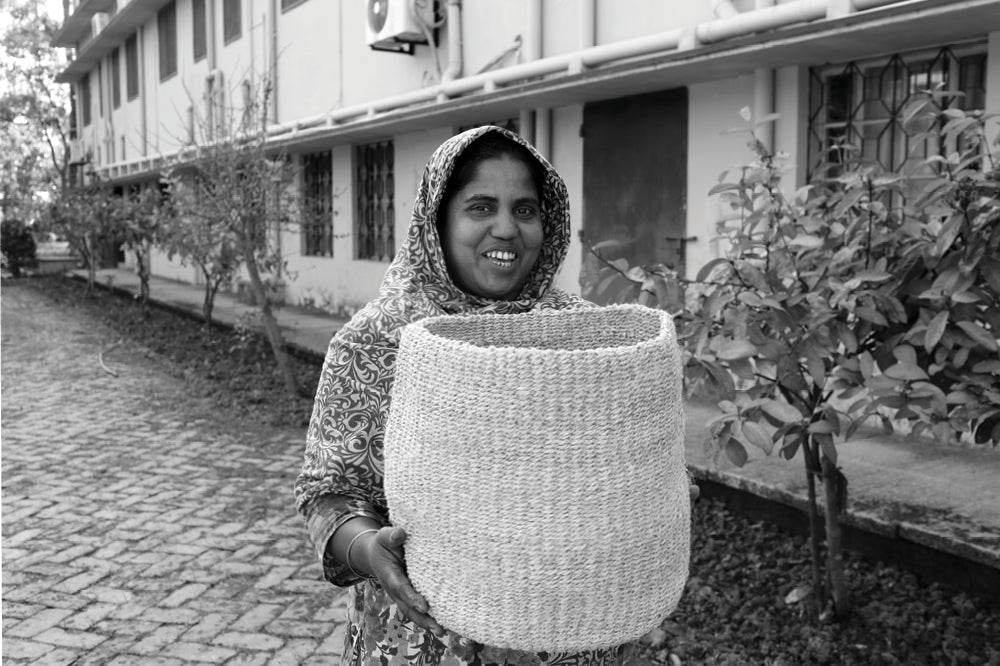 Fair trade artisans - Bangladeshi woman holds basket she made by hand out of natural jute