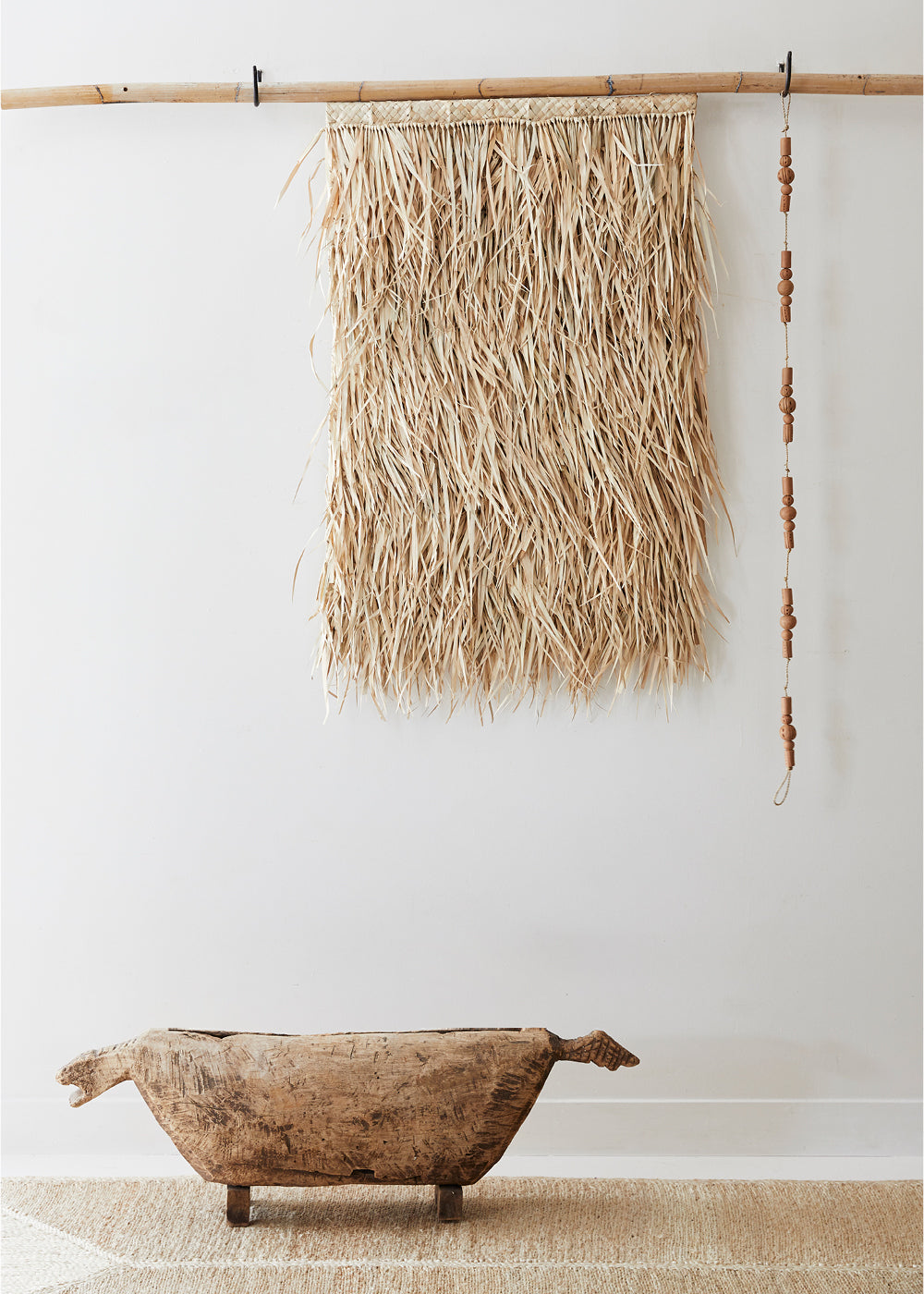 woven wall hanging - handmade palm leaf wall hanging hung on bamboo pole.