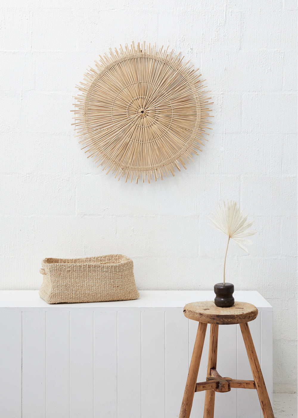 woven wall hanging - circular woven grass wall hanging on plain white wall with woven jute basket and vase in front of it.