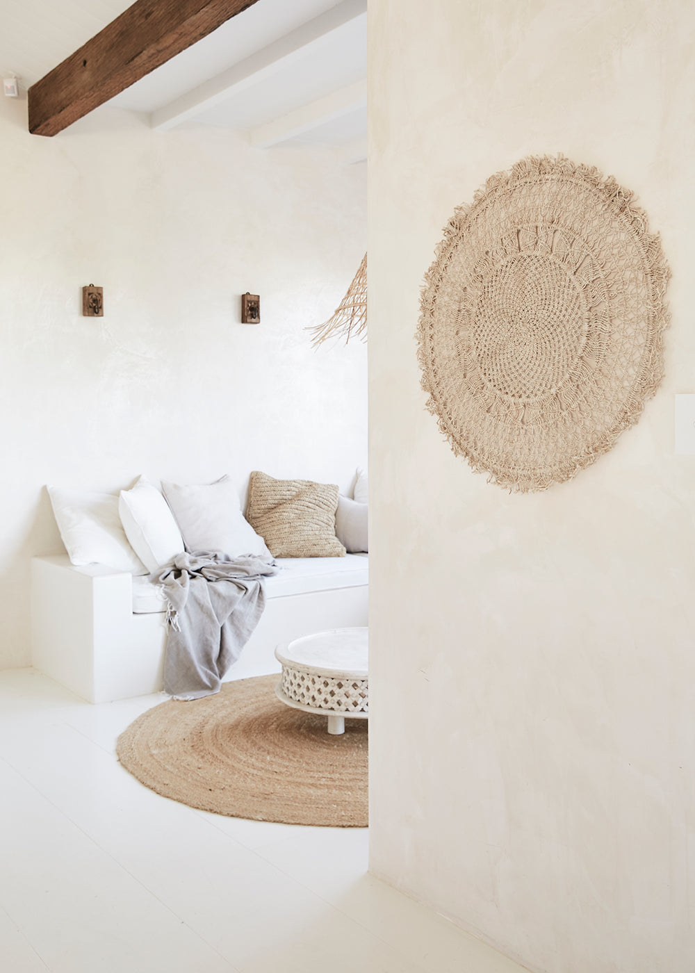 woven wall hanging - round handwoven mandala wall hanging on plain white wall with sofa and cushions in the background.