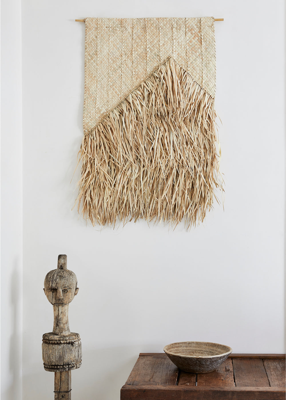 woven wall hanging - woven palm leaf wall hanging with fringe on white wall.