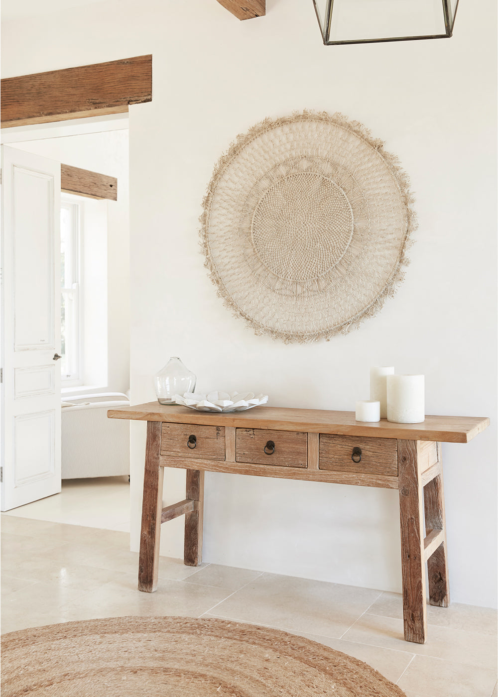woven wall hanging - round handwoven mandala wall hanging on plain white wall with light wood console table in front of it.