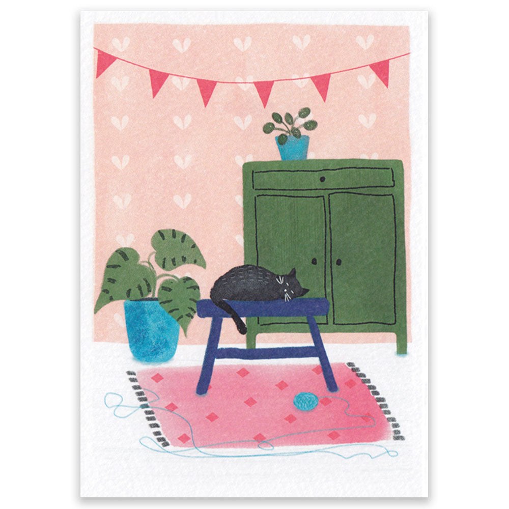 A postcard showing a pink interior, a sleeping cat and some plants