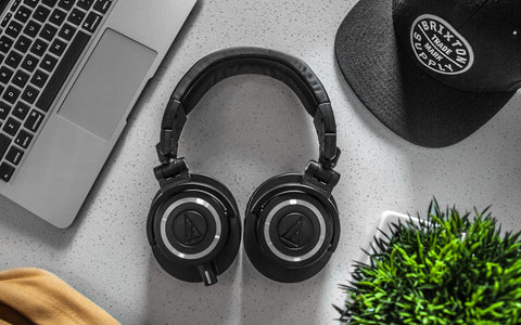 Wireless headphones on grey desk with computer, cap and succulent plant
