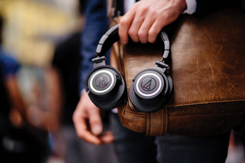 Audio-Technica Headphones Held Against Brown Satchel