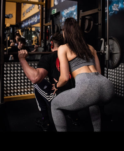 man lifting weights woman helping behind