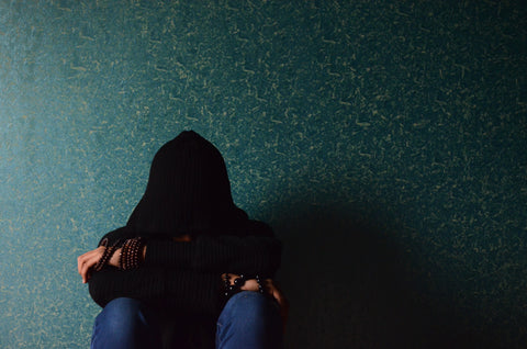 Depressed woman sitting against blue wall