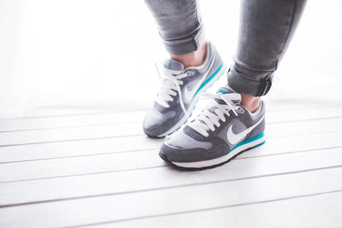 Woman wearing Nike trainers on wooden gym floor