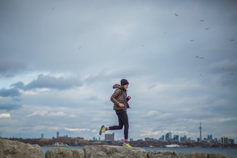 Woman running in cold weather gear against grey sky