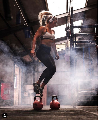 Woman jumping in gym with smoke in the background wearing EarHugz
