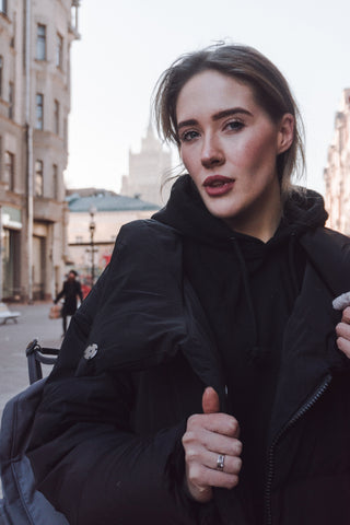 Woman in black coat in city