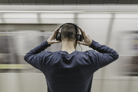 Man with headphones waits for a train