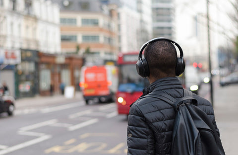 Man in wireless headphones stands on London street waiting for a bus