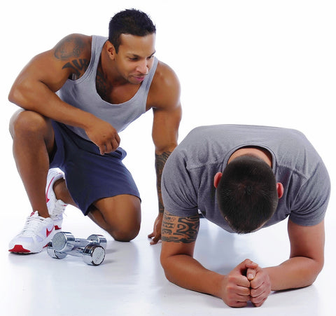 Personal Trainer in Gym Planking Position