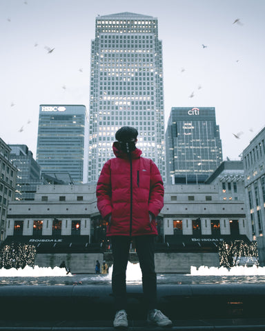 Man wearing red puffa jacket in a city