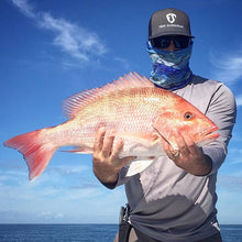 man holding red grouper fish wearing free sunshields sunglasses and waves neck gaiter mask