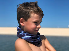 boy on blue ocean beach wearing shark bait neck gaiter scarf