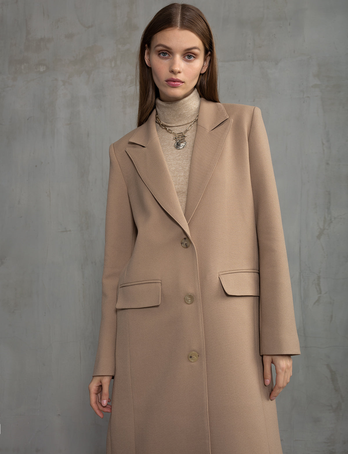 Woman wearing tan, oversized, blazer coat with turtleneck