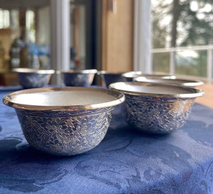 potalagate silver small offering bowl with auspicious designs engraved on a blue table with natural lighting