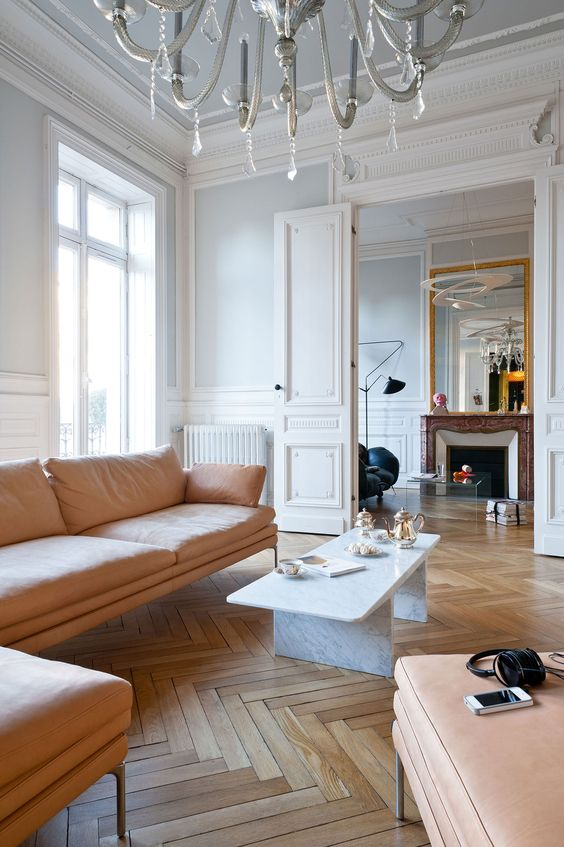 spring in Paris, a light and bright living room with herringbone floors and a flesh toned leather sofa