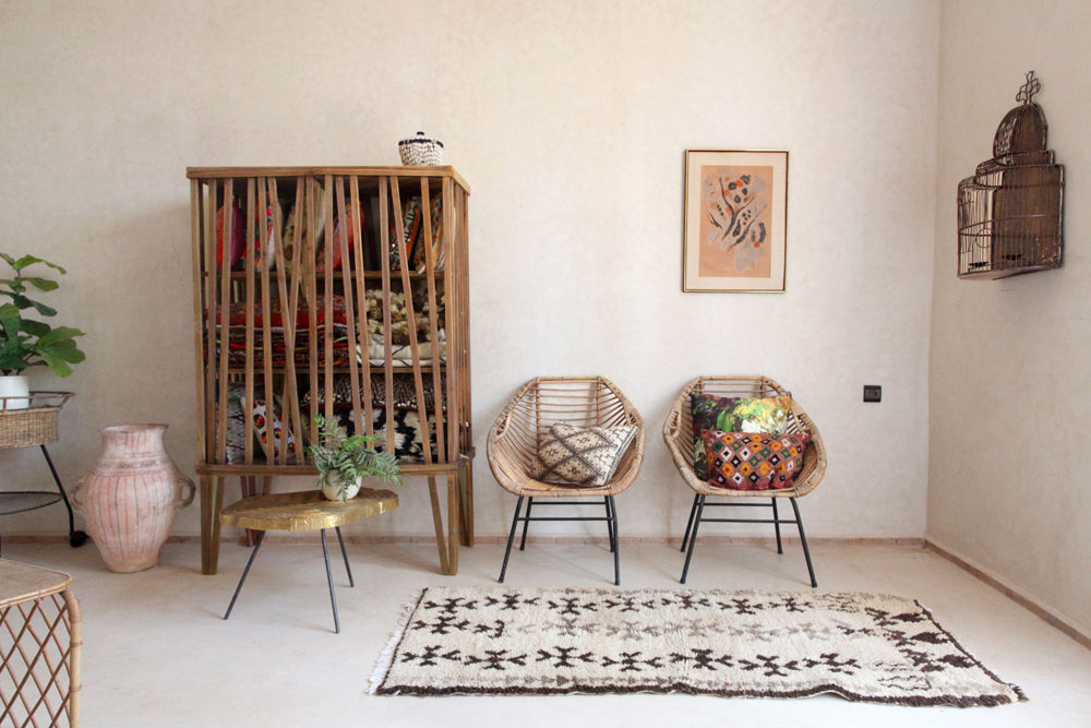 a small vintage azilal rug sits next to berber pottery and a brass wall mounted bird cage in the gardener's house bed and breakfast in marrakesh, morocco