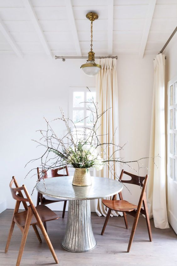 Spring decorating with freshly foraged branches as dining table decor, hans wegner sawbuck dining chairs and an angelo mangiarotti inspired table