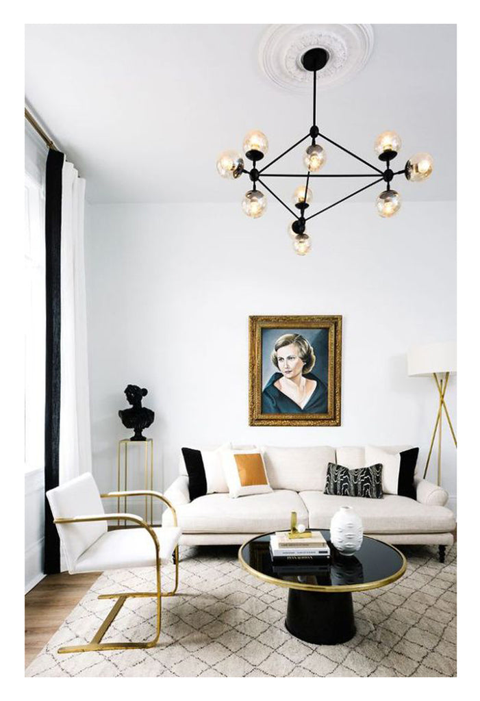 Modern Hollywood glamour is Beni Ourain rug with small scale diamond pattern, a chic white linen sofa, brass MCM cantilever armchair, and black sputnik chandelier. Black and white Mid Century Modern style at its best.