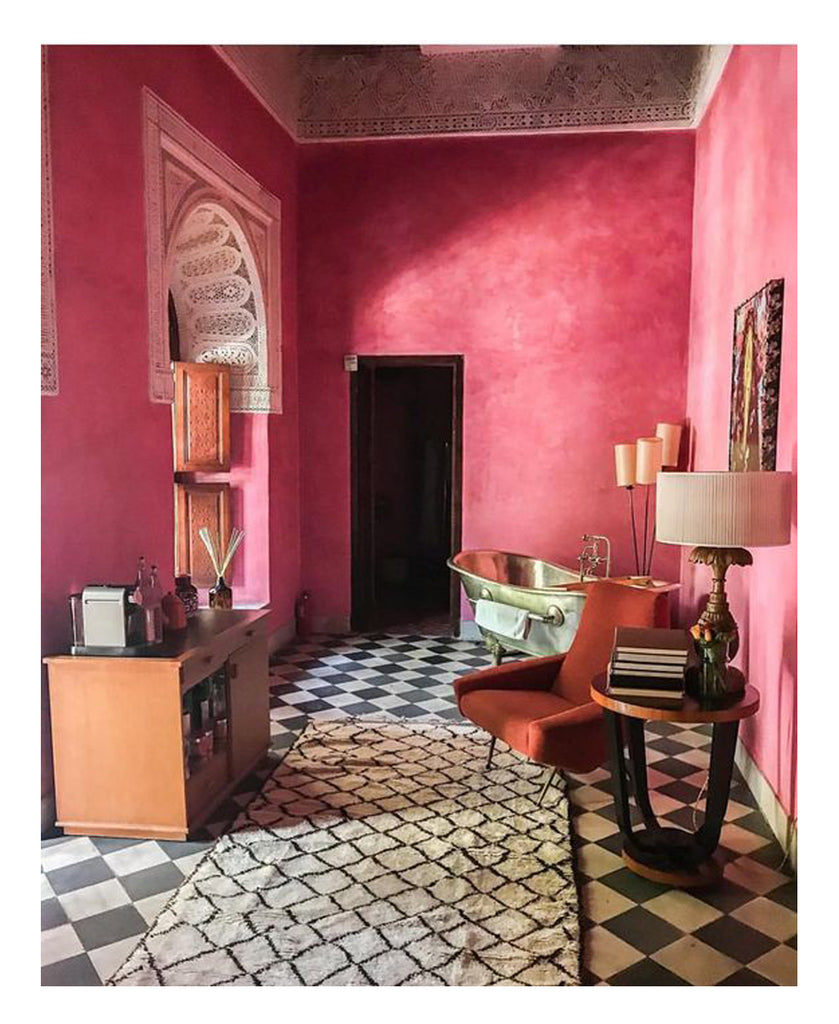 A bold, classic Beni Ourain contrasts with black and white tiles in a Moroccan riad in Marrakesh. Pink tadelakt walls are the backdrop to Mid Century Modern design classics including a glam 50s Marco Zanuso style Italian armchair.