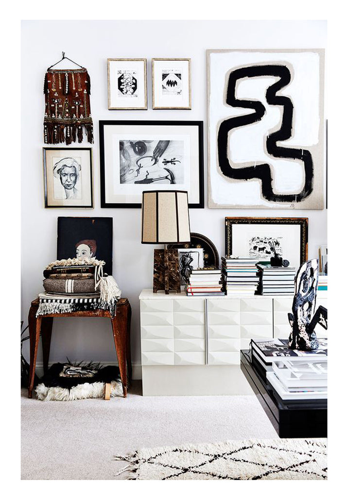 A subtle Beni Ourain with classic diamond pattern provide the balance for Malene Birger's graphic interior styling. Bold black and white art mingle with ethnic textiles over a laquered Mid Century Modern sideboard.