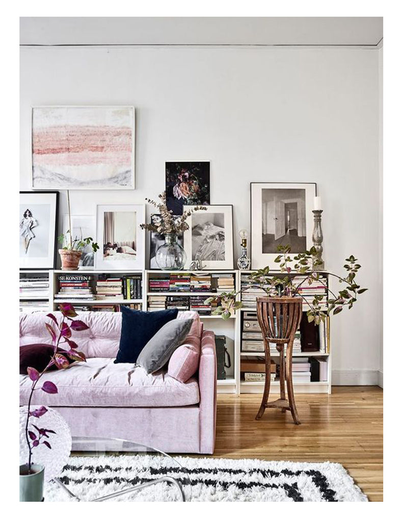 A striped Beni Ourain rug grounds a Danish modern living room with a modern touch of pink. The perfect pink velvet sofa, Dahlia by MELIMELI, was featured in Elle Decoration Sweden. The Berber + Danish mix is affordable modern luxury.