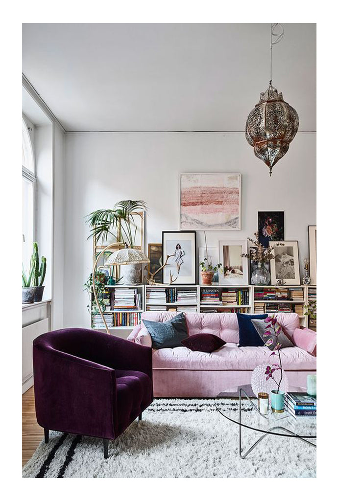 A Beni Ourain rug, a purple velvet Mid Century Modern armchair, a Moroccan brass pendant lamp, and the pink Dahlia sofa by MeliMeli are just a bit of the magic that put this room on the cover of Elle Decoration Sweden.