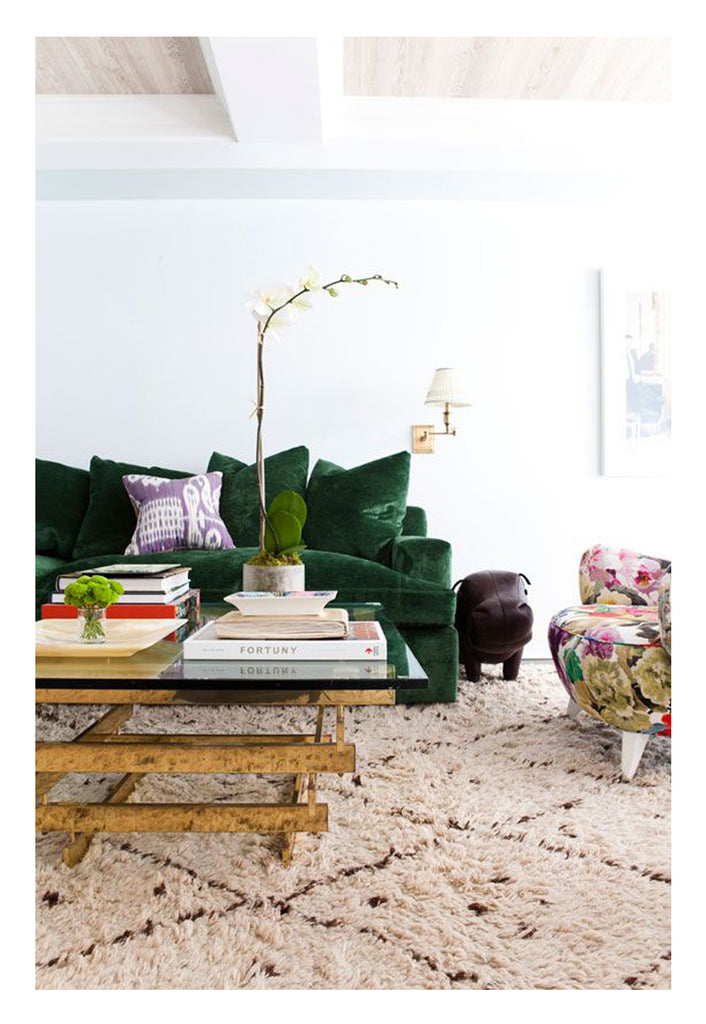 A charming Beni Ourain with large scale diamond and dot pattern, styled with a gorgeous green velvet sofa, a floral textile armchair, and a statement brass iron coffee table.