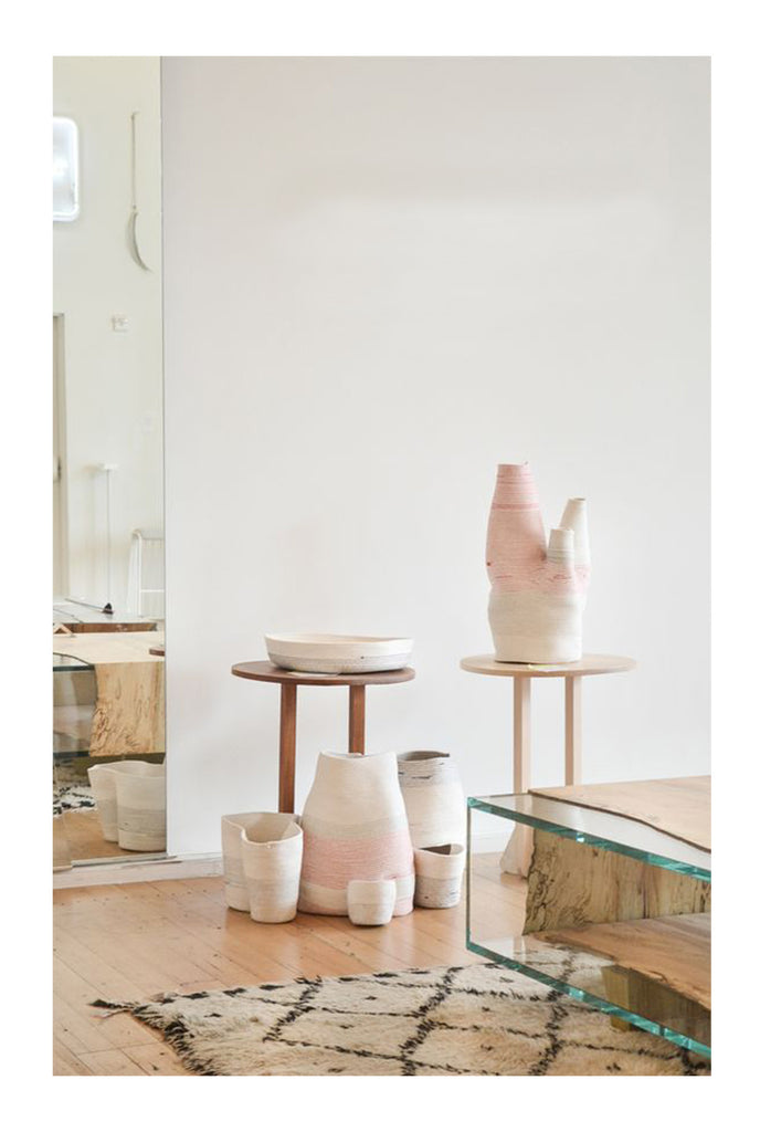 Blush pink ceramics, simple modern tables and a stunning beni ourain rug. Throw in a fused glass natural edge coffee table and you've got make you smile style.