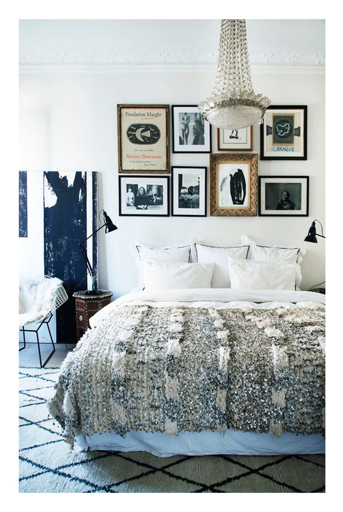 A bold graphic beni ourain on the floor in a Danish glam bedroom complete with traditional french chandelier and some eye catching black and white gallery wall art.