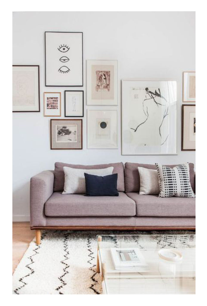 The only thing more chic than a pink sofa is a lavendar sofa with a zig zagging beni ourain, a glass waterfall coffee table, and an impressive gallery wall. Soft feminine decor at its best.