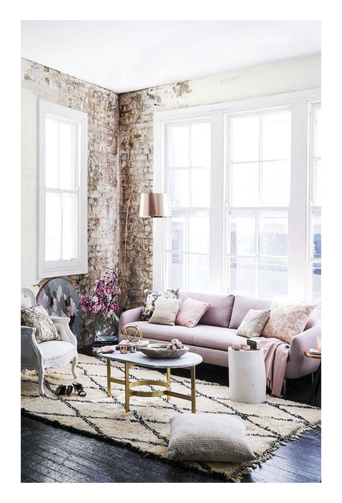 This iconic loft living space is flooded with light. The classic patterned beni ourain rug is a statement that is elevated by a beautiful blush pink sofa and the soft morning light.
