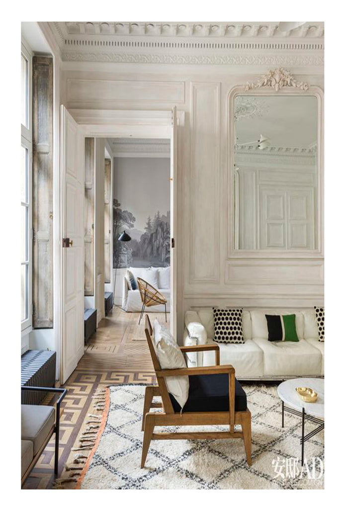 Is there any space more elegant, more of a pleasure to design and look at than a parisian style apartment. Add one beni ourain rug, a sculptural modern armchair and some restrained luxury - a classy white linen sofa - and you've got a dream space with strikingly beautiful design.