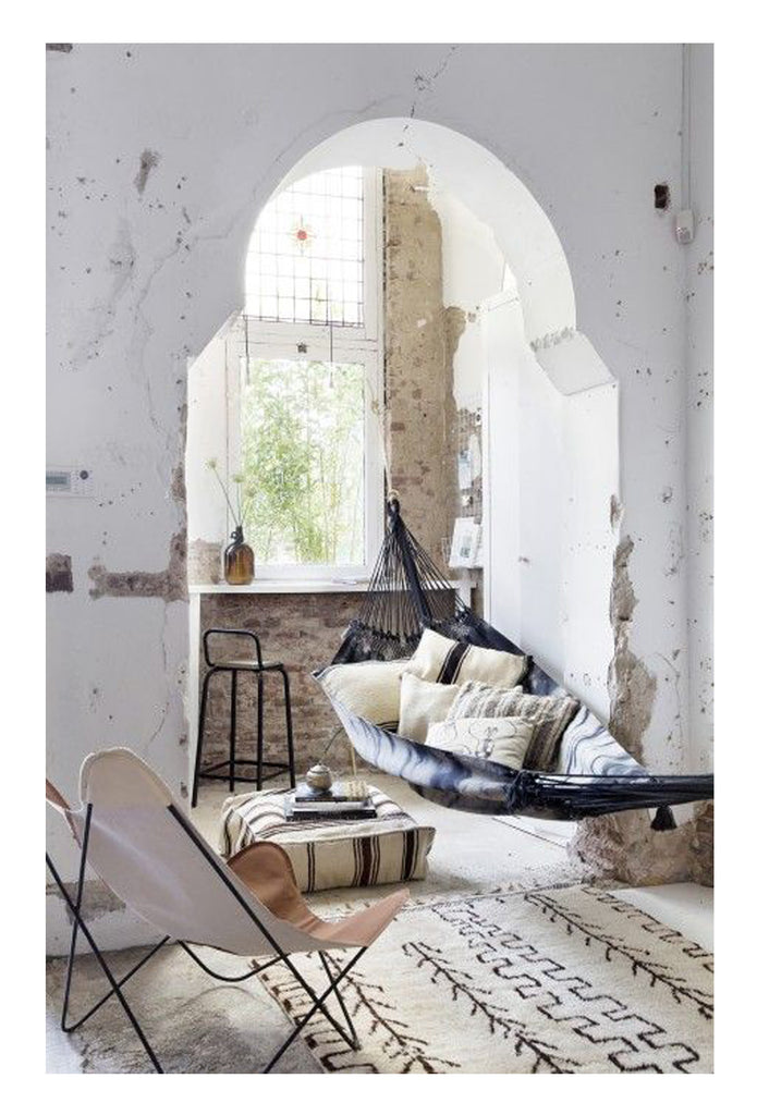 A beni ourain rug in its element, on the floor of an old, original Moroccan riad in Marrakesh, Morocco and styled with a butterfly chair and a hammock. The beautiful arched doorway stands in the background, a testiment to classic Islamic architecture.